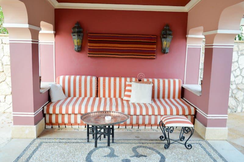 Weiches Sofa in einem Café im Freien auf der Straße und einer Tabelle für Tee in der arabischen Art mit Bögen lizenzfreie stockbilder