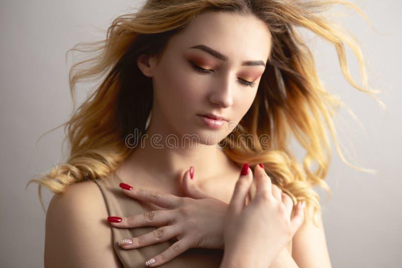 Weiches Studioporträt einer schönen jungen Frau, Mädchengesicht mit dem gelockten Haar zerzaust vom Wind, das Konzept der Natursc lizenzfreie stockfotografie