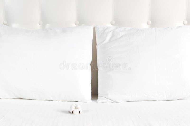 Weiches wei?es gestepptes Kissen und Baumwollblume im Bett auf dem Hintergrund der wei?en ledernen gesteppten Kopfende Sauberes K lizenzfreies stockfoto