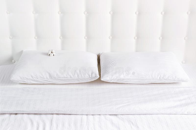 Weiches wei?es gestepptes Kissen und umfassende Bettdecke im Bett auf dem Hintergrund der wei?en ledernen gesteppten Kopfende Sau stockbild
