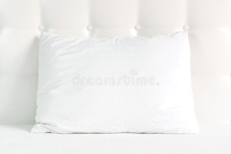 Weiches wei?es gestepptes Kissen im Bett auf dem Hintergrund der wei?en ledernen gesteppten Kopfende Sauberes Kissen, Teil der Be stockbilder