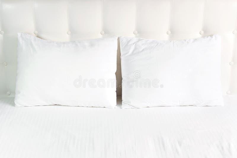 Weiches wei?es gestepptes Kissen im Bett auf dem Hintergrund der wei?en ledernen gesteppten Kopfende Sauberes Kissen, Teil der Be lizenzfreie stockfotografie