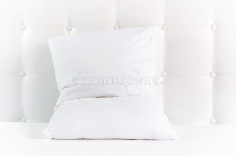 Weiches wei?es gestepptes Kissen im Bett auf dem Hintergrund der wei?en ledernen gesteppten Kopfende Sauberes Kissen, Teil der Be lizenzfreies stockfoto