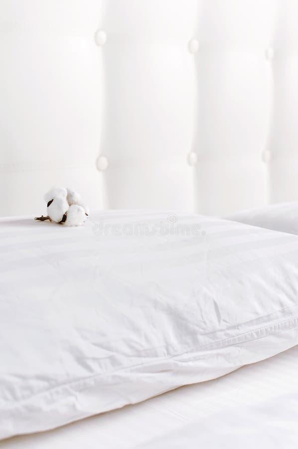 Weiches wei?es gestepptes Kissen und Baumwollblume im Bett auf dem Hintergrund der wei?en ledernen gesteppten Kopfende Sauberes K stockfotos