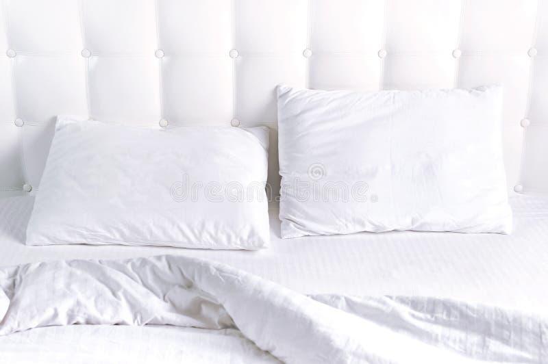 Weiches wei?es gestepptes Kissen und umfassende Bettdecke im Bett auf dem Hintergrund der wei?en ledernen gesteppten Kopfende Sau stockfoto