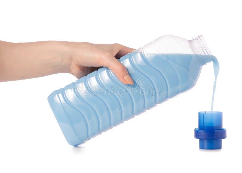 Weichmachungsmittelconditioner in der blauen Plastikflasche in der Hand lokalisiert auf weißem Hintergrund stockfotografie