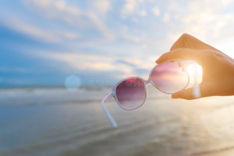 Weichzeichnung auf der Frauenhand, die Sonnenbrille über Meer und Sandy hält stockfotografie