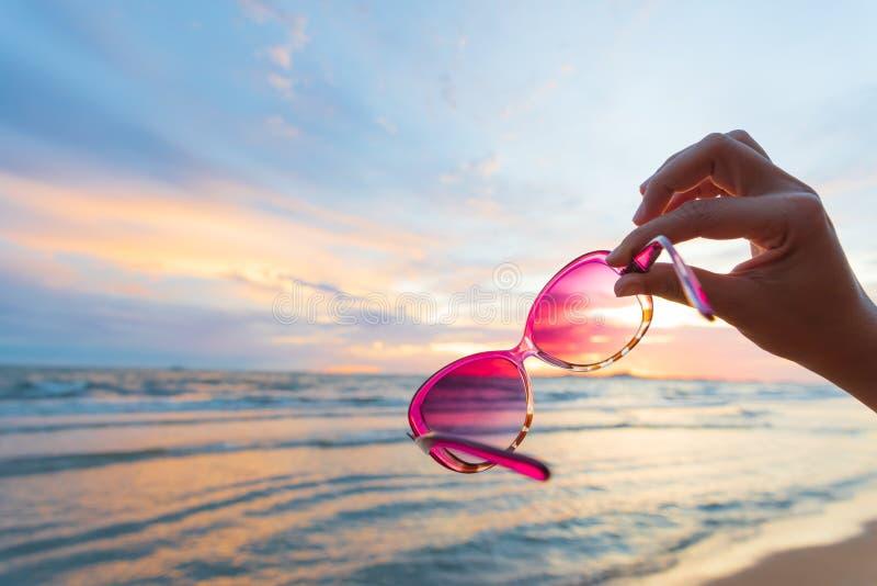 Weichzeichnung auf der Frauenhand, die Sonnenbrille über Meer und Sandy hält stockfotos
