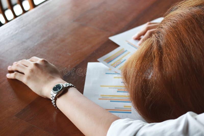 Weichzeichnung der müden überarbeiteten jungen Geschäftsfraubiegung hinunter Kopf auf Diagrammen im Büro stockfotos