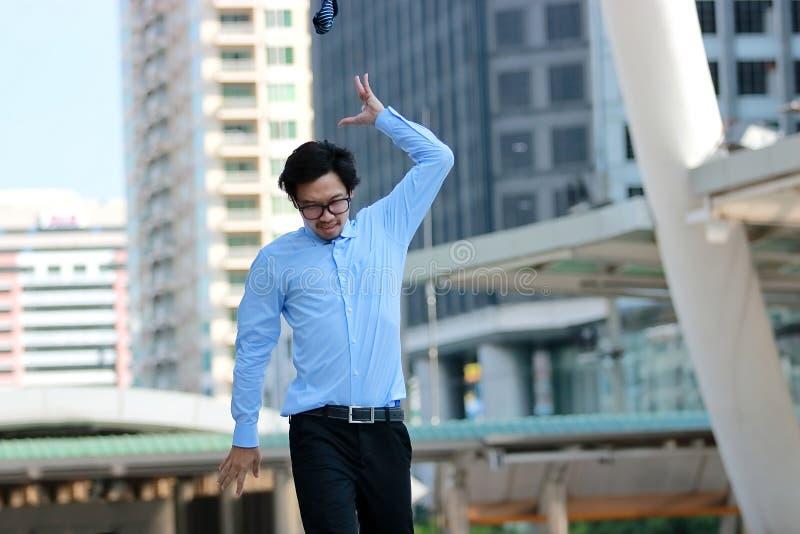 Weichzeichnung des frustrierten betonten jungen asiatischen Geschäftsmannes, der seine Krawatte im städtischen Gebäudestadthinter lizenzfreie stockbilder