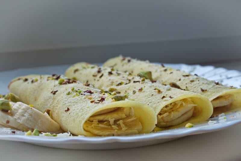 Weichzeichnungsabschluß oben von 3 Krepppfannkuchen mit der Erdnussbutter und Bananen überstiegen mit Schokolade und Cocosschnitz lizenzfreie stockfotografie