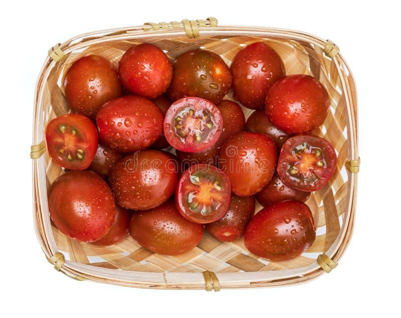 Weiden- Korb mit Kirsch-Tomaten Mini-kumakos geschnitten in halbes und in ganzes Mit Wassertropfen lizenzfreie stockfotos