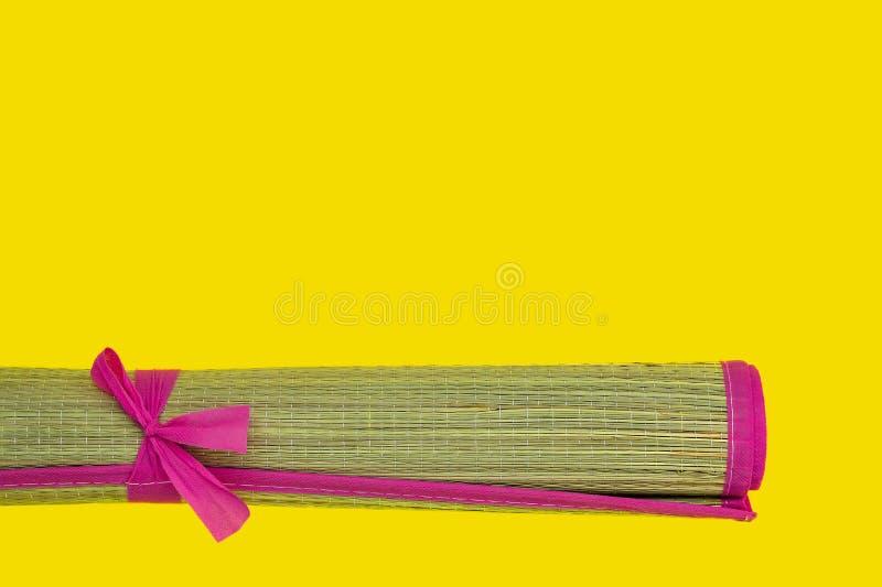 Weidenbaststrandmatte mit dem rosa Rand gerollt in Rolle auf einem gelben Hintergrund Heißes Sommer- und Strandthema Kopieren Sie stockfotografie