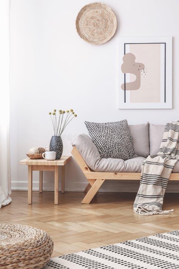 Weidendekorationen und eine Malerei auf einer weißen Wand über einem hölzernen Sofa mit Kissen in einem hellen Wohnzimmerinnenrau stockfotografie