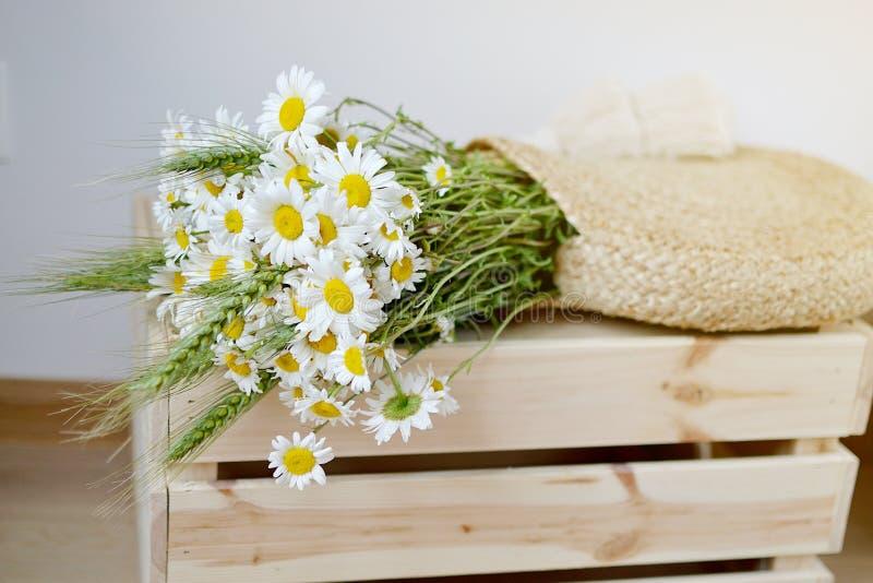Weidenhandtasche mit Blumen Kamille, Holzkiste, Sommer Concep stockbilder