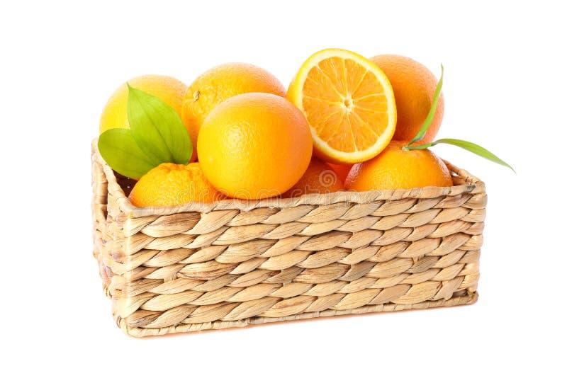 Weidenkorb mit den reifen Orangen lokalisiert auf weißem Hintergrund stockfotografie