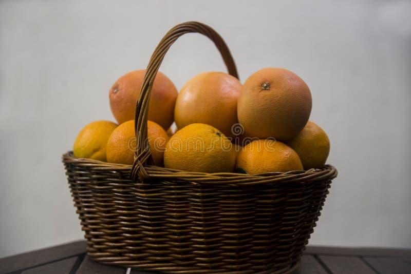 Weidenkorb mit Orangen und Pampelmusen auf weißem Hintergrund stockfotografie