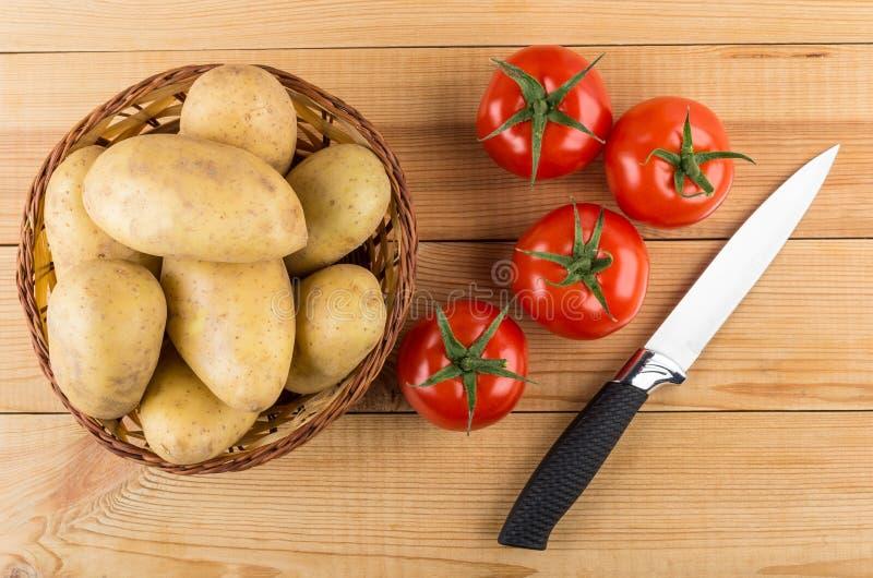 Weidenkorb mit rohen Kartoffeln, roten Tomaten und Küchenmesser stockbilder