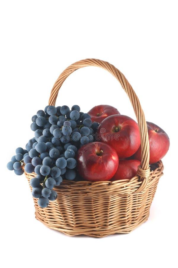 Weidenkorb mit roten Äpfeln und blauen Trauben stockfotos