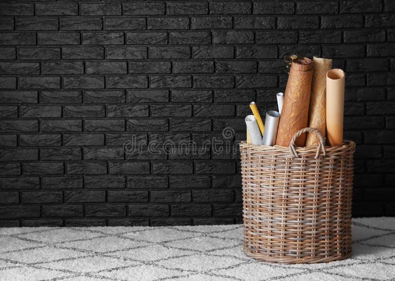 Weidenkorb mit verschiedenen gerollten Papieren nahe dunkler Backsteinmauer zuhause stockfotografie