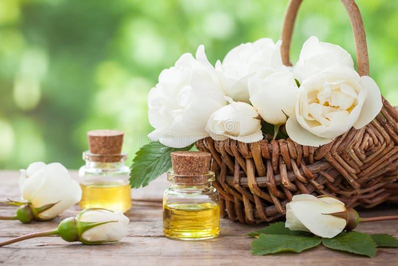 Weidenkorb mit weißen Rosen Bündel und Ölflaschen lizenzfreies stockfoto