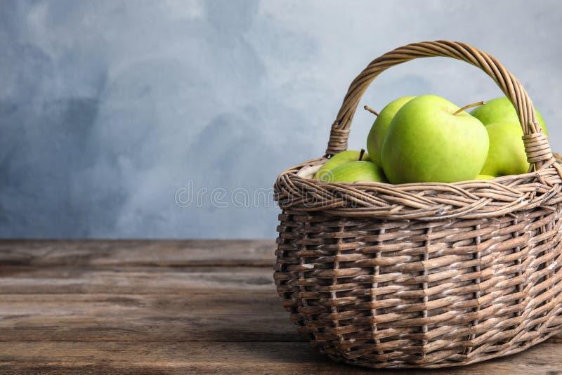 Weidenkorb von frischen reifen grünen Äpfeln auf Holztisch gegen blauen Hintergrund stockfoto
