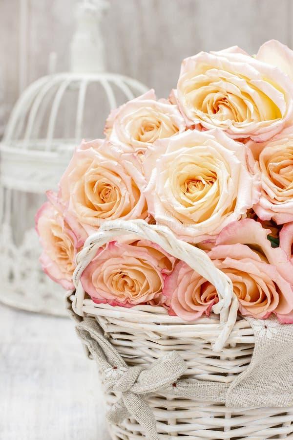 Weidenkorb von Rosen auf rustikalem Holztisch lizenzfreie stockfotos
