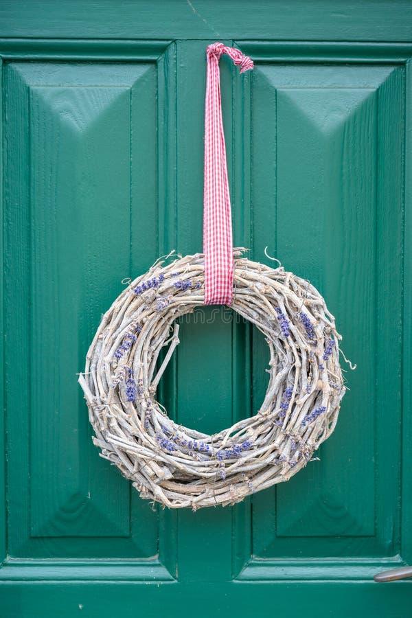 Weidenniederlassungskranz mit den Lavendelblumen, die an der alten grünen Tür hängen stockbild
