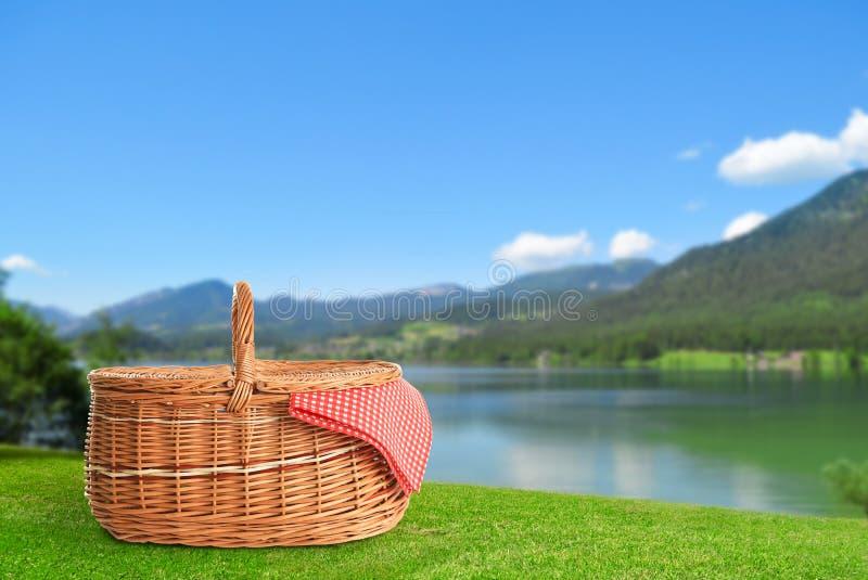 Weidenpicknickkorb auf Gras nahe Fluss und Bergen stockfoto