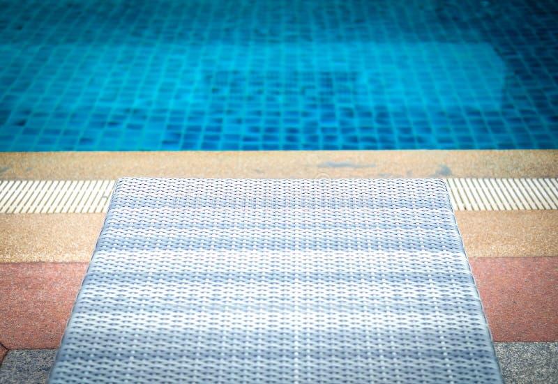 Weidenrattanpoolsonnen-Bett deckchair am Swimmingpool lizenzfreie stockbilder