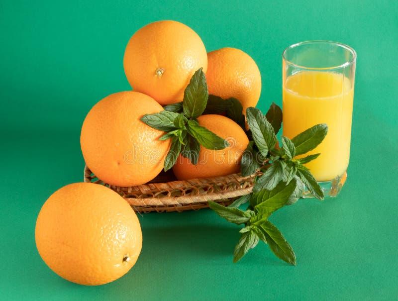 Weidensch?ssel mit den Orangen verziert mit Minze, nahe bei einem Glas mit Orangensaft auf einem gr?nen Hintergrund stockbilder