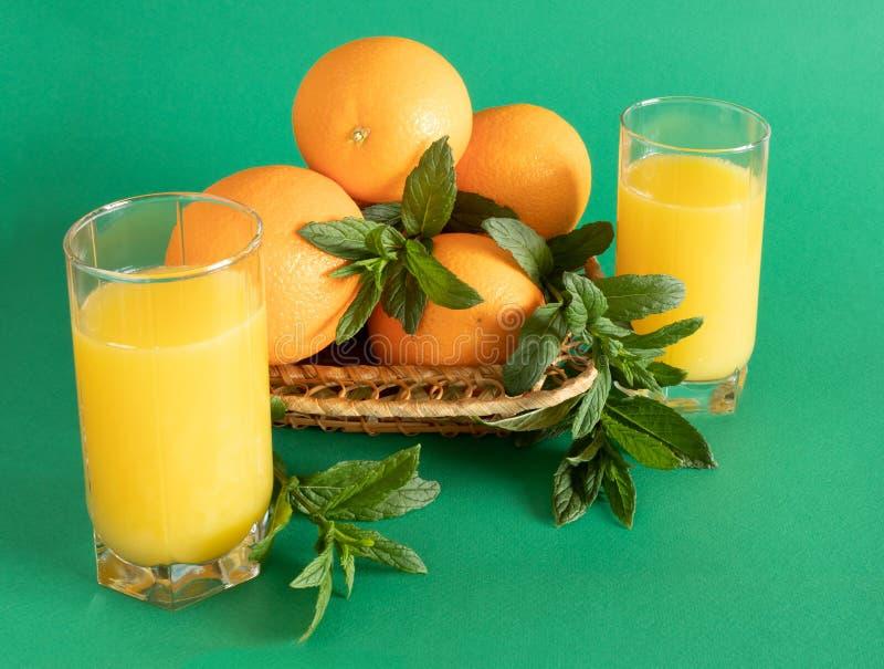 Weidensch?ssel mit Orangen und Minze auf gr?nem Hintergrund lizenzfreie stockfotos