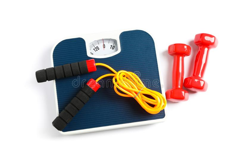 Weigh scales, skipping rope and dumbbells isolated stock photo