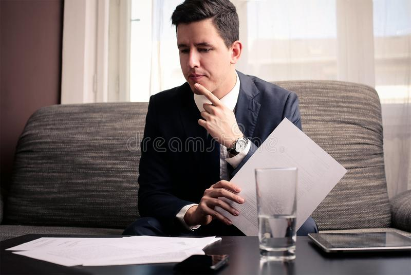 Weighing different options. Young businessman weighing different options stock photo
