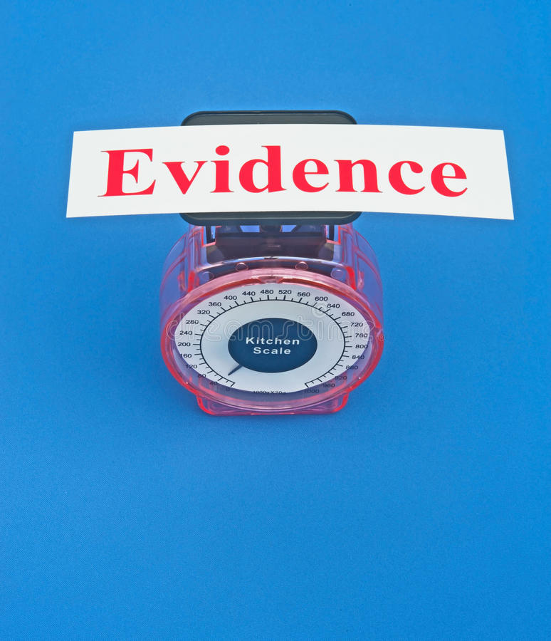 Weighing the evidence. Text ' evidence ' in red letters on white on top of weighing scales, concept of weighing the evidence stock photography