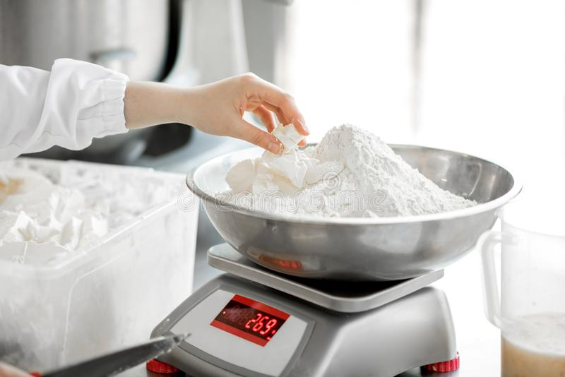 Weighing flour for baking at the manufacturing royalty free stock photo