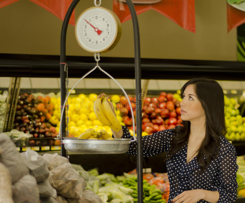 Weighing fruits at the supermarket. Young beautiful woman weighing some bananas at a grocery store stock photography