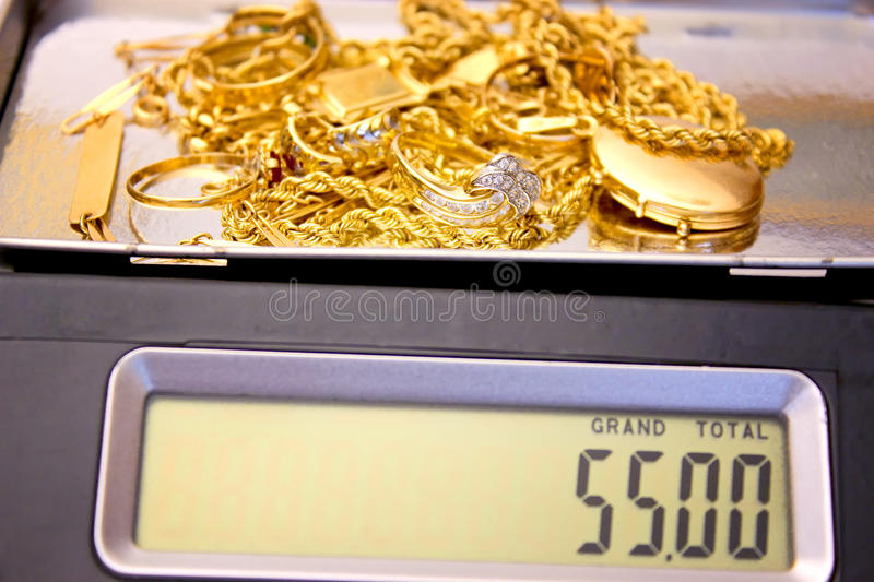 Weighing gold. Gold jewelery weighing on a digital scale, photography stock photo