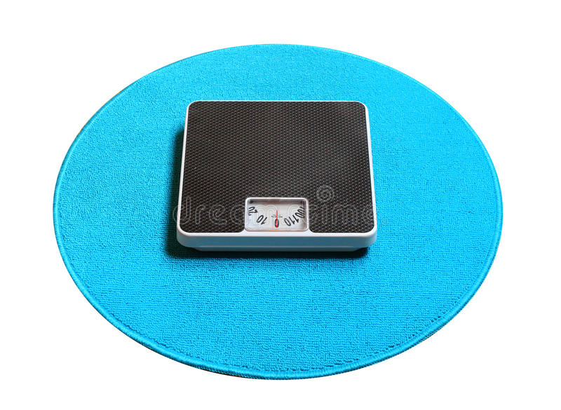 Weighing machine on a blue carpet. Retro style weighing machine on a blue carpet. Sliming, dieting and healthy lifestyle theme stock image
