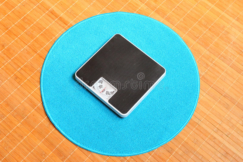 Weighing machine on a blue carpet. Retro style weighing machine on a blue carpet. Sliming, dieting and healthy lifestyle theme royalty free stock photo