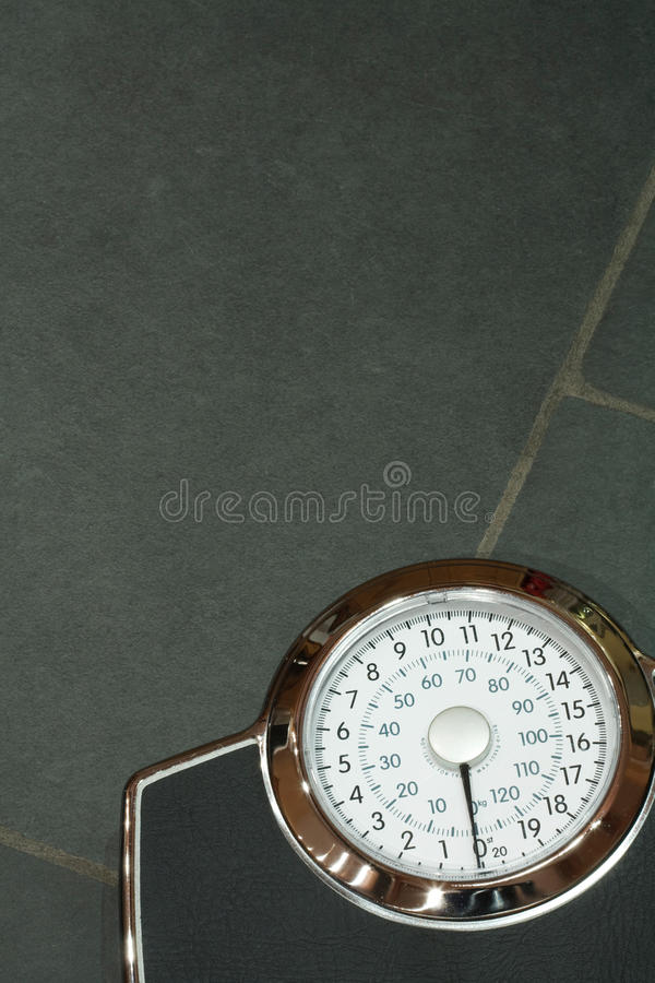 Weighing scales. On a slate floor with copyspace royalty free stock photography