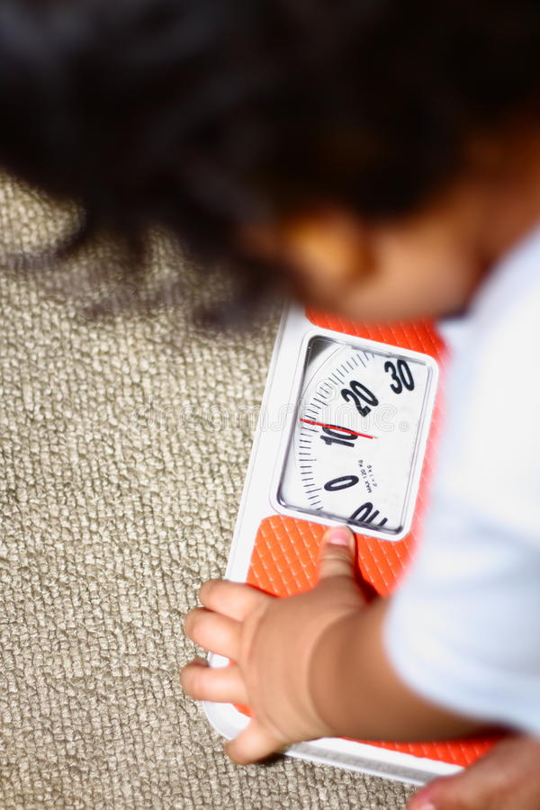 Weighing Scales. A toddler weighing himself on a Scales stock photos