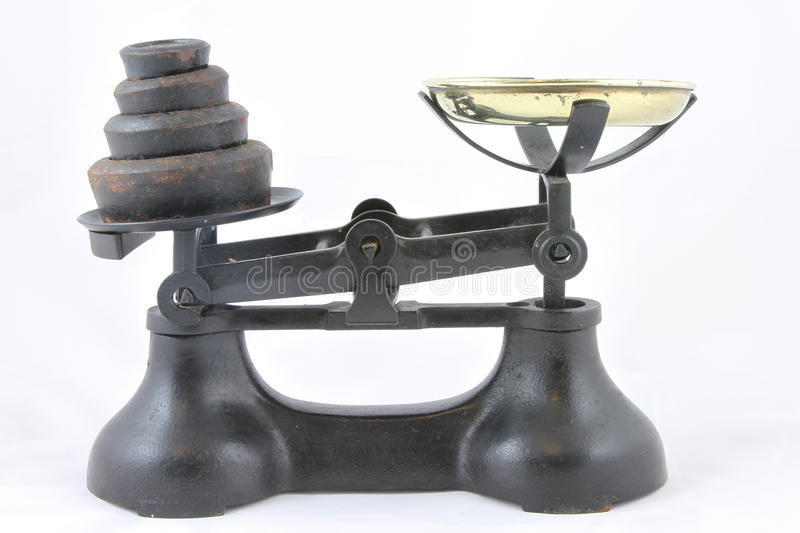 Weighing scales. Antique weighing scales with brass bowl and rusty black weights royalty free stock photo