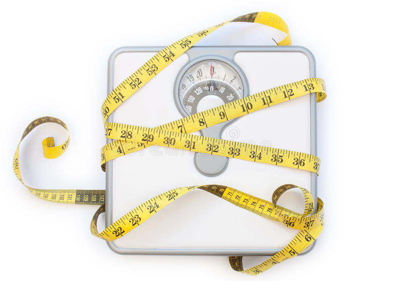 Weighing scales. Yellow tape measure wrapped around a weighing scales machine royalty free stock photography