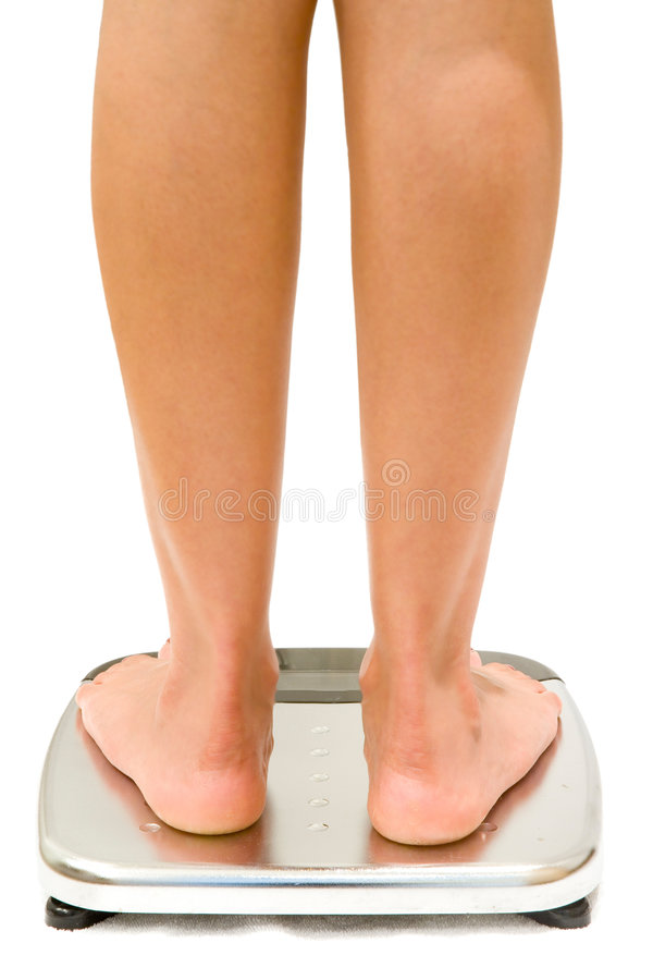 Weighing Scales Isolated. Woman stands on weighing scales isolated on white stock photography