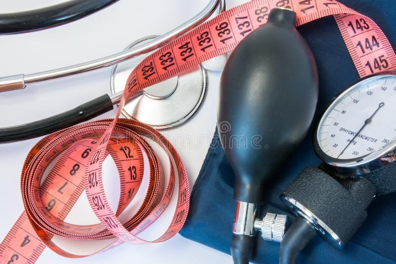 Weight gain or loss and high or low blood pressure concept. Measuring tape, stethoscope and sphygmomanometer. Effect of obesity, i. Ncreased body weight or royalty free stock photos