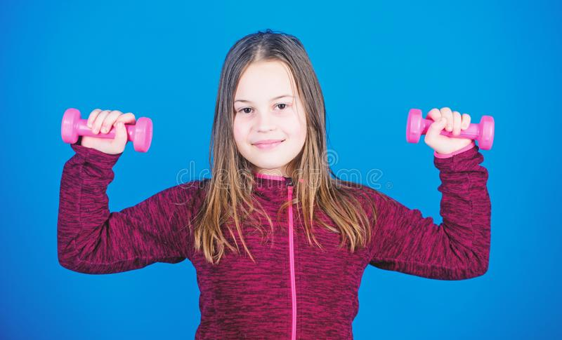 Weight lifting for muscules. Childhood activity. Fitness diet for energy health. workout of small girl has dumbbell. Sport success. Happy child sportsman with stock image