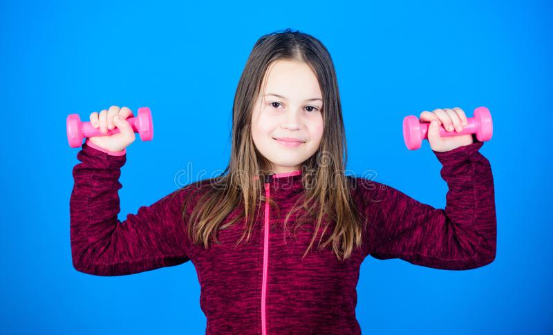 Weight lifting for muscules. Childhood activity. Fitness diet for energy health. workout of small girl has dumbbell. Sport success. Happy child sportsman with royalty free stock image