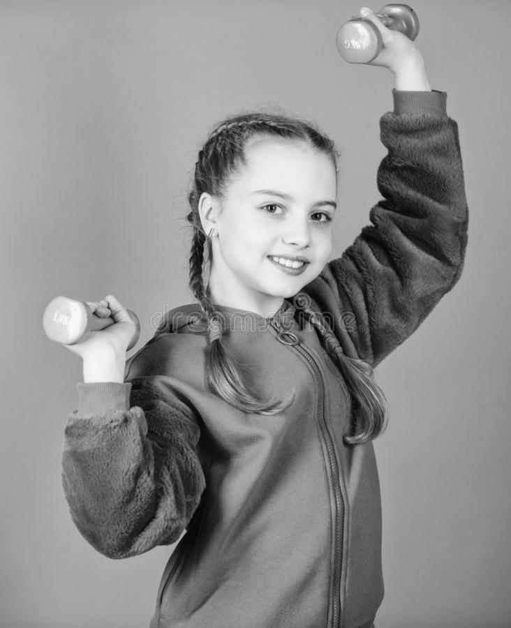 Weight lifting for muscules. weight loss. workout of small girl hold dumbbell. Sport success. Fitness diet for energy. Health. Happy child sportsman with stock photos
