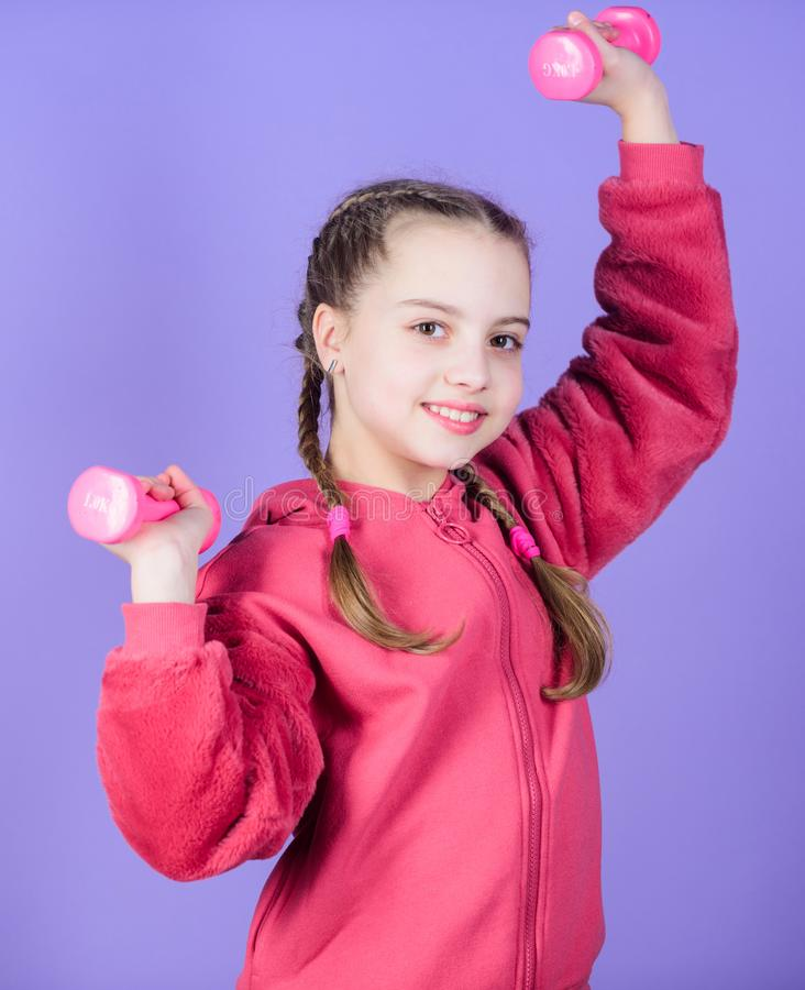 Weight lifting for muscules. weight loss. workout of small girl hold dumbbell. Sport success. Fitness diet for energy. Health. Happy child sportsman with stock image